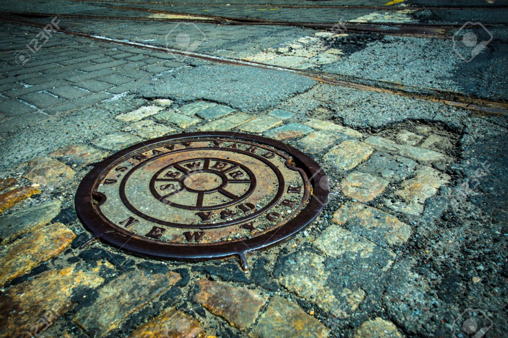 41772401-New-York-City-manhole-drain-cover-on-cobblestone-and-asphalt--Stock-Photo